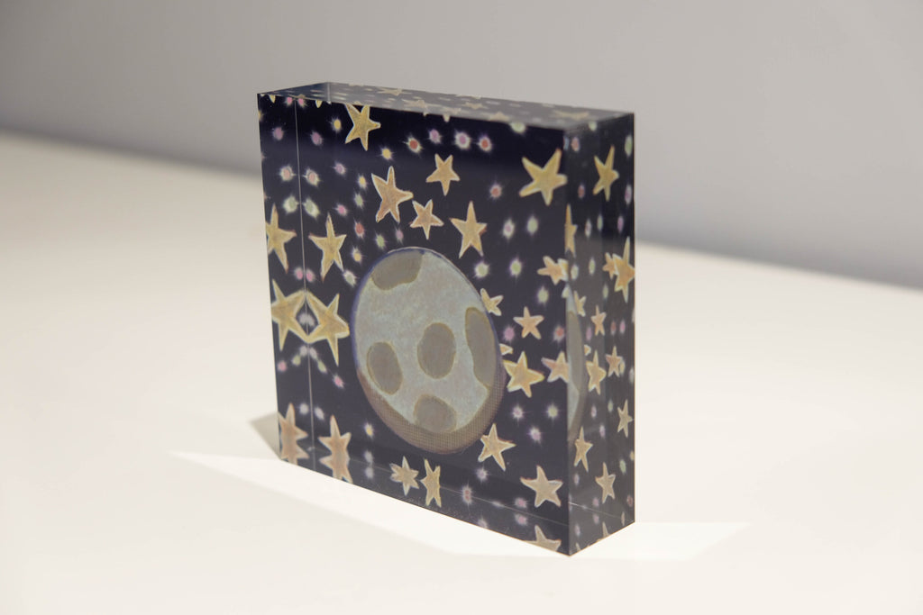 Tilted view of Acrylic block depicting outer space with a blue background and golden stars with Earth in the center