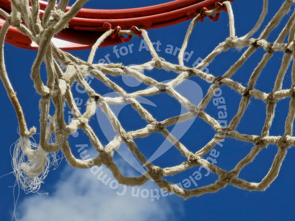 Close up view of white basketball netting and red basketball rim against blue sky