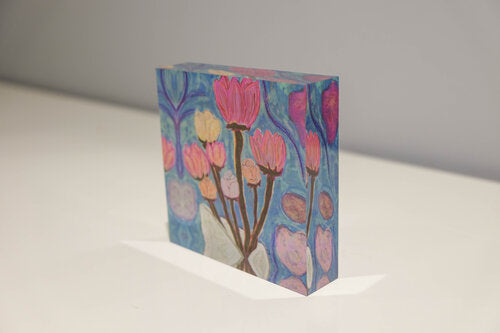 Tilted view of Acrylic block with light blue background and bouquet of pink, yellow, and light orange flowers with brown stems