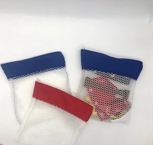 Three white mesh laundry bags, two with a blue fabric strip and one with a red fabric strip at the zipper