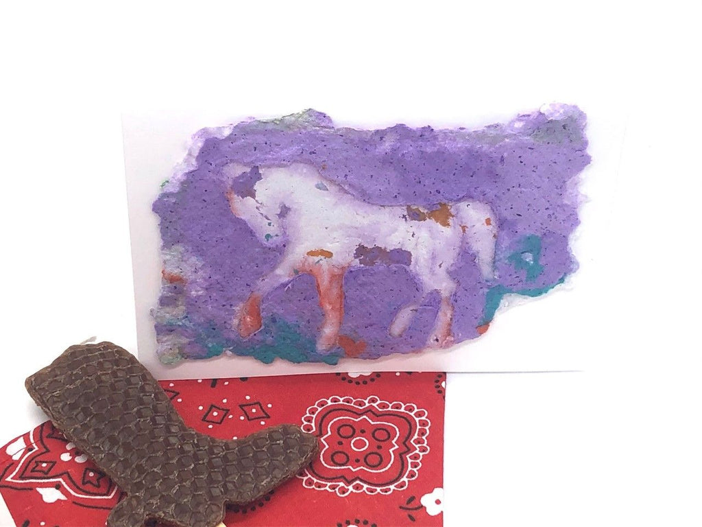 card with handmade paper design of a horse. vivid colors of purple, and blue. Red bandana and brown boot candle also displayed