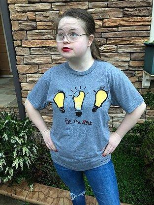 Young woman wearing gray tshirt with three yellow lightbulbs above Be The Light slogan