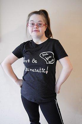 Young girl with brown hair wearing red glasses and a gray t-shirt that says Don't Be Dramanatic