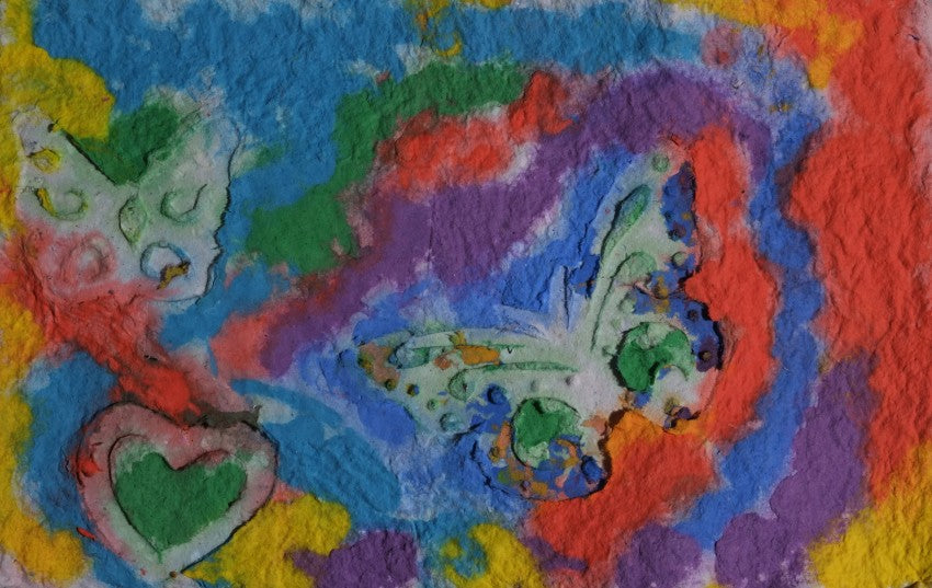 Pigment on recycled paper artwork with blue, green, red, purple and yellow background with two white butterflies and one white heart over top