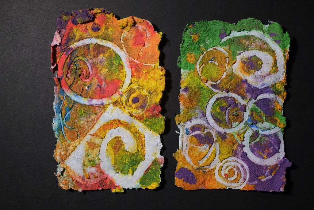 Two pieces of Pigment on recycled paper artwork with white circles and swirls against a background of yellows, greens and purples