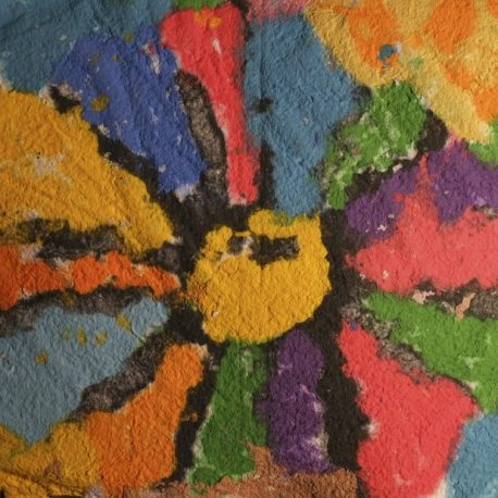 Pigment on recycled paper artwork of a large flower with yellow inside and blue, red, and green colored petals