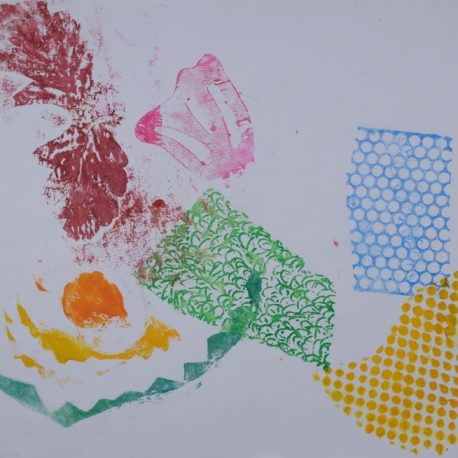 Ink on paper artwork with stamps of various colors and patterns.  Green swirl, blue honeycomb, yellow dots, pink flower, orange dot