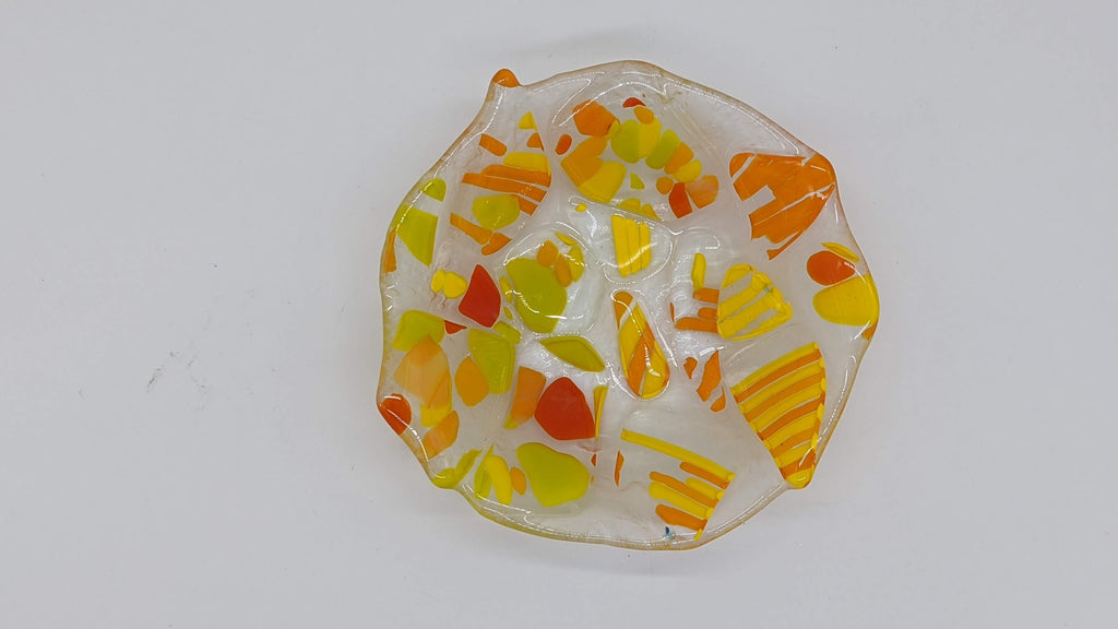 Clear glass bowl with specs of Yellow and orange through out