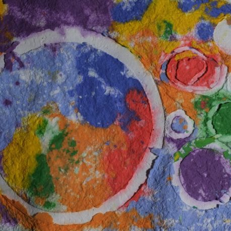 Pigment on recycled paper artwork with white circles against a background of purple, yellow, green, orange and blue colors