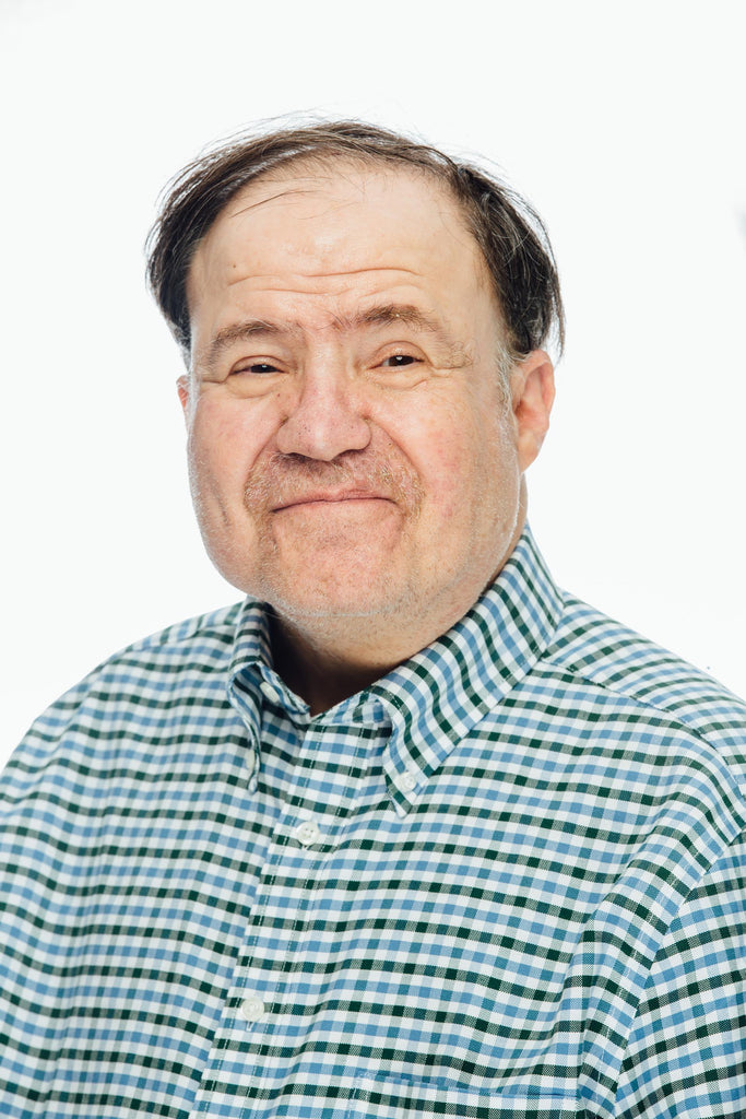 Smiling man with brown hair and green, blue and white checked polo shirt