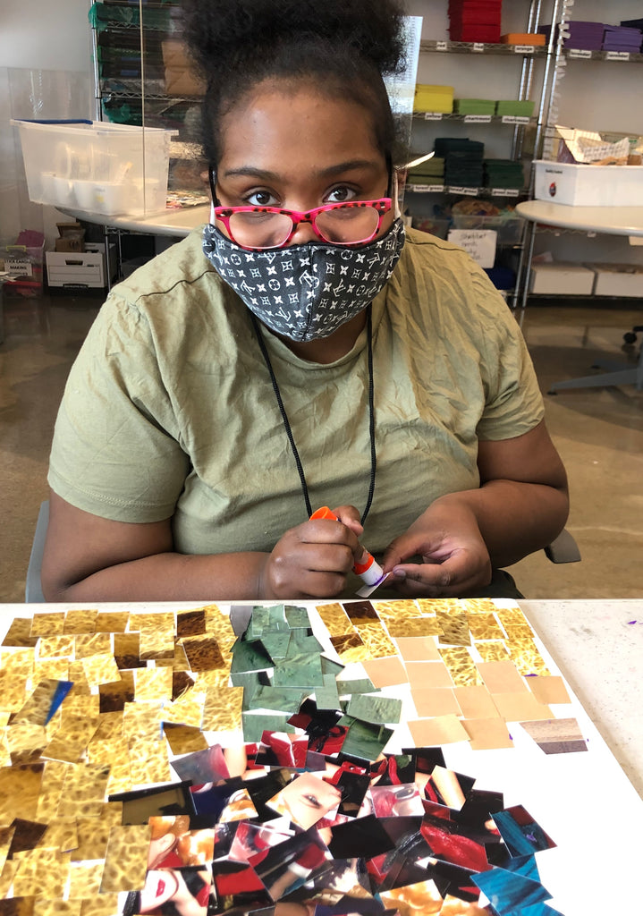 Female participant with pink eye glasses looking toward the camera and glueing a piece of her mosaic art.  Mosaic art is sitting on the table in front of her.  It is made of of square of photographs in shades of cream, yellow, red and green.