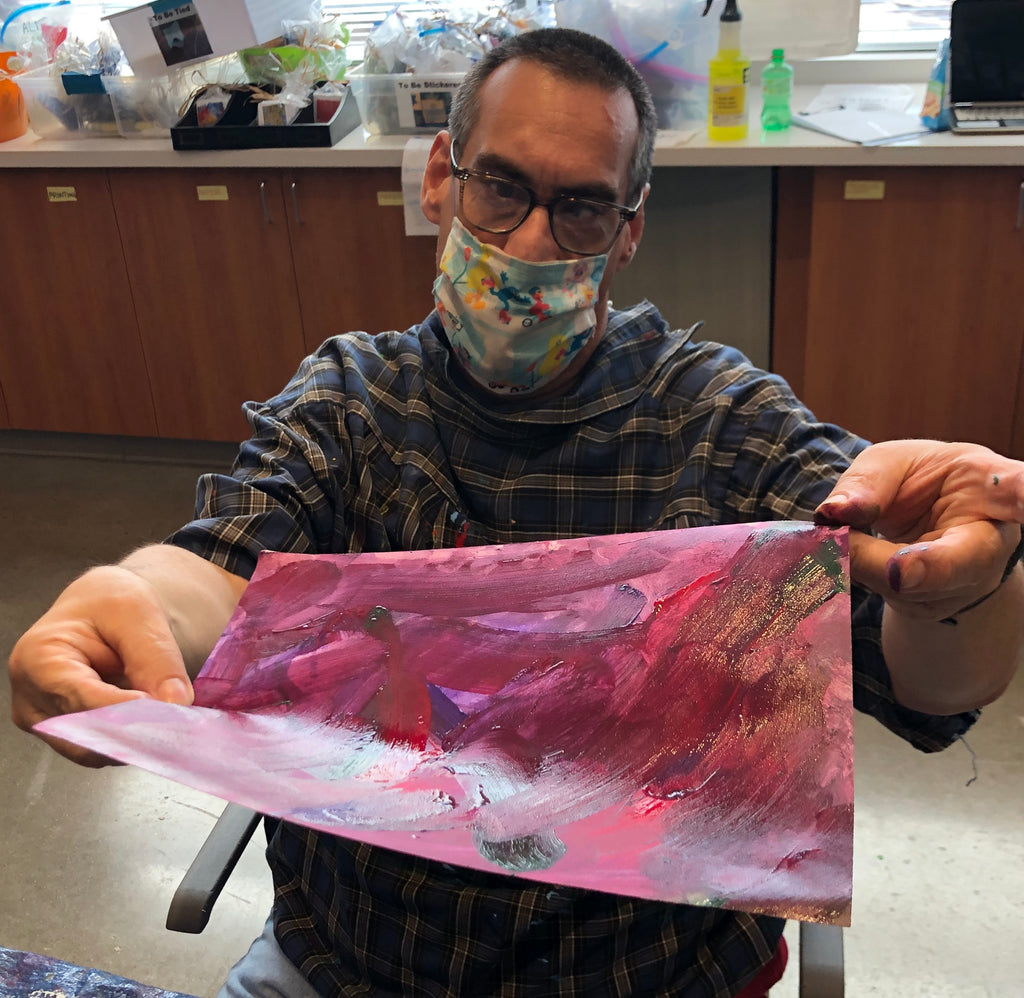 Male participant with a Seasame street mask holding a maroon and purple painting.