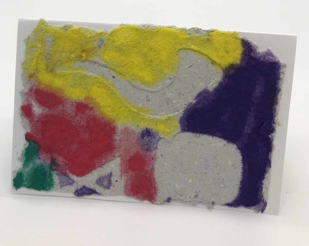 Yellow, purple, red and green background with a shofar in natural paper color on top.  There are two indistinguishable random  shapes on top also.