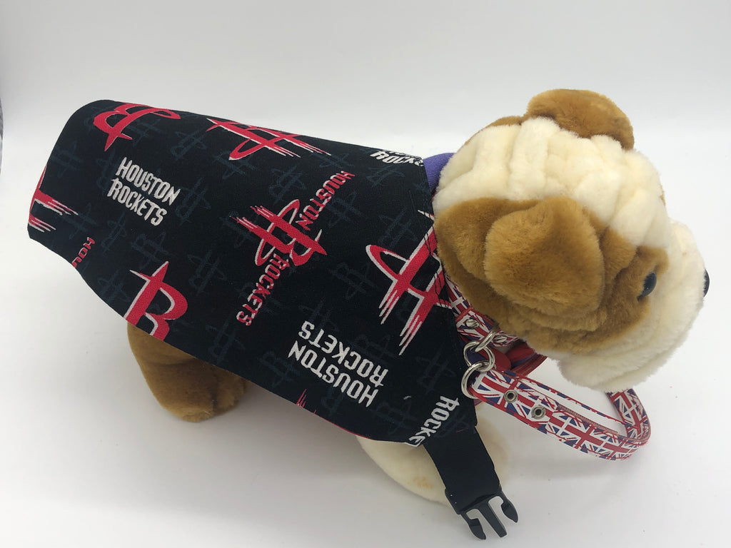 Photo of a small stuffed brown and cream dog with a black and red triangular bandana with the Houston Rockets logo in red and white across it's back.