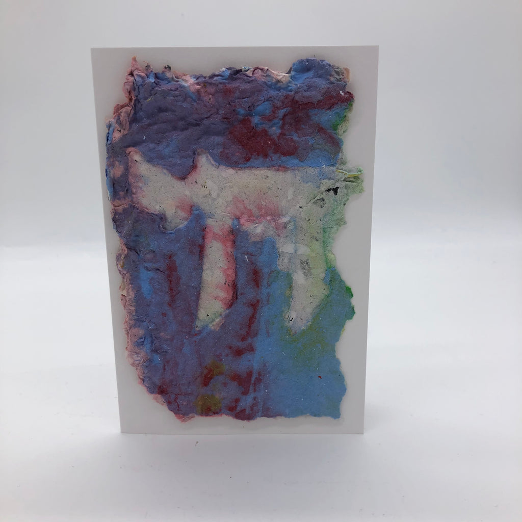 Handmade paper greeting card with white Chai against light blue mixed with maroon background
