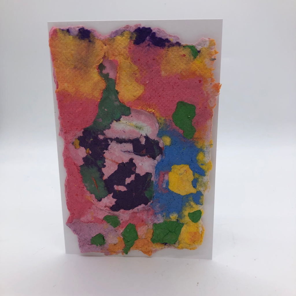 Handmade paper card in several colors including salmon, yellow, green, blue and purple.  The cupcake on top has green, light pink and purple,