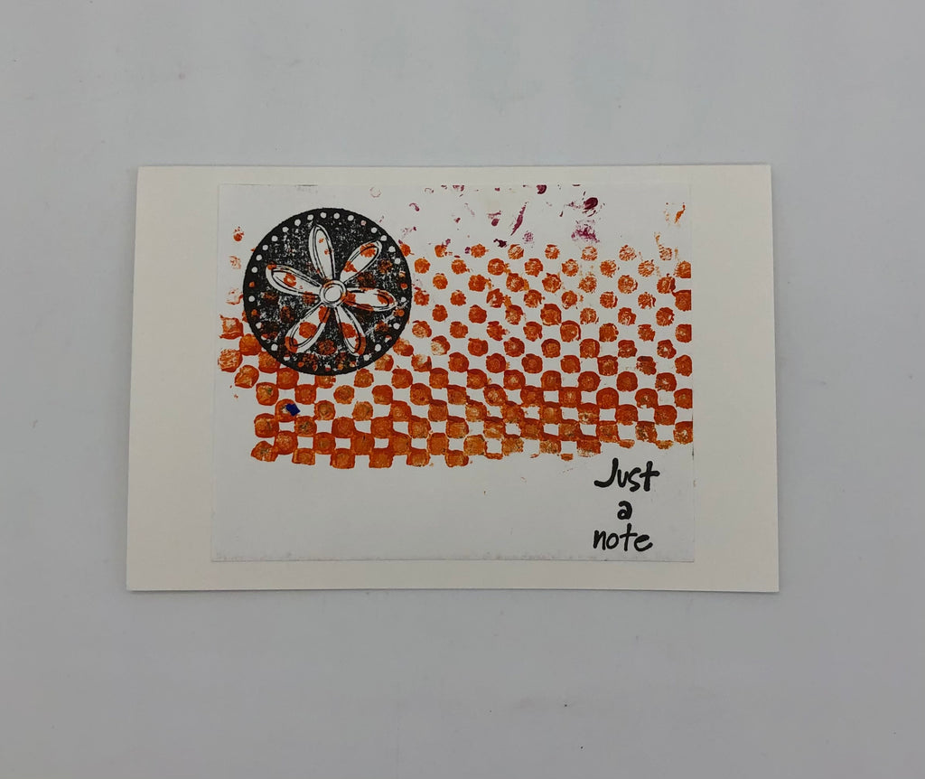 "White greeting card with orange cirlces arranged in rows and columns with a freeform border at the bottom and left side.  On top of that is a circle stampe with a daisy in the middle.  This is on the upper left side. In the bottom right in black is stamped ""Just a Note"""
