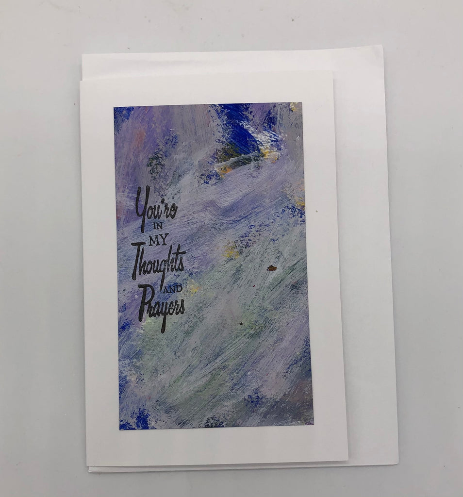 "White greeting card with large acrylic painting in white and purple.  On top of the painting is stamped ""You're in my thoughts and prayers"" in black on the left hand side."