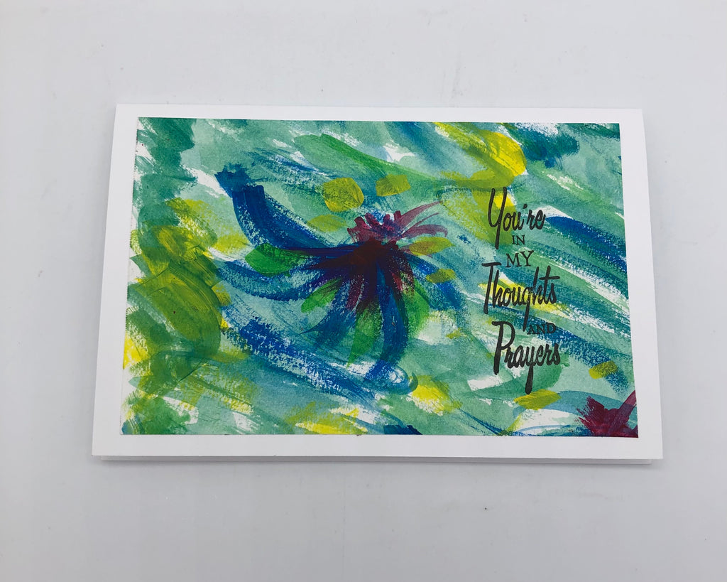 "White greeting card with large acrylic painting in shades of greens, blues and yellow.  Some of the white background is showing through.  In the center ti a partial swirl in blue..  On top of the painting is stamped ""You're in my thoughts and prayers"" in black on the right hand side."