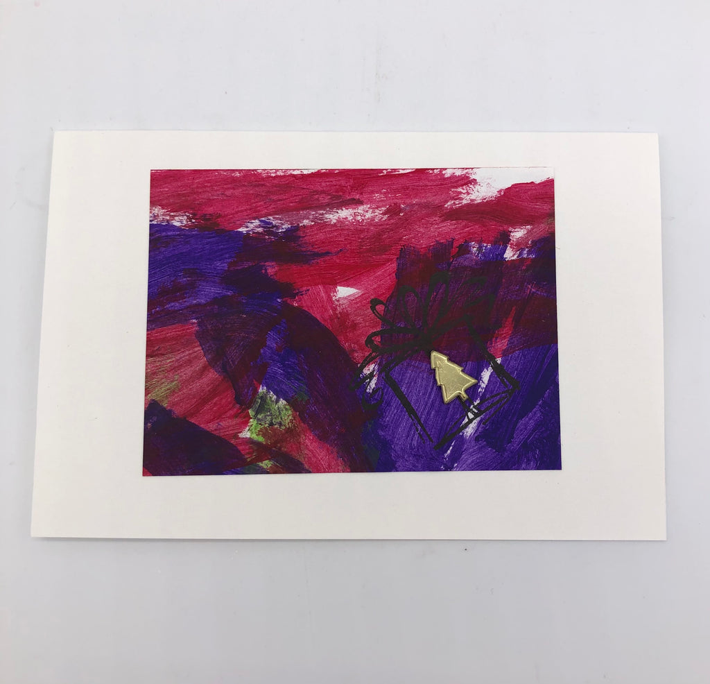 White greeting card with acrylic painting in purple and maroon.  There is a stamp of a gift box with bow outlined in black with a small gold metal christmas tree glued on where the gift is shown.