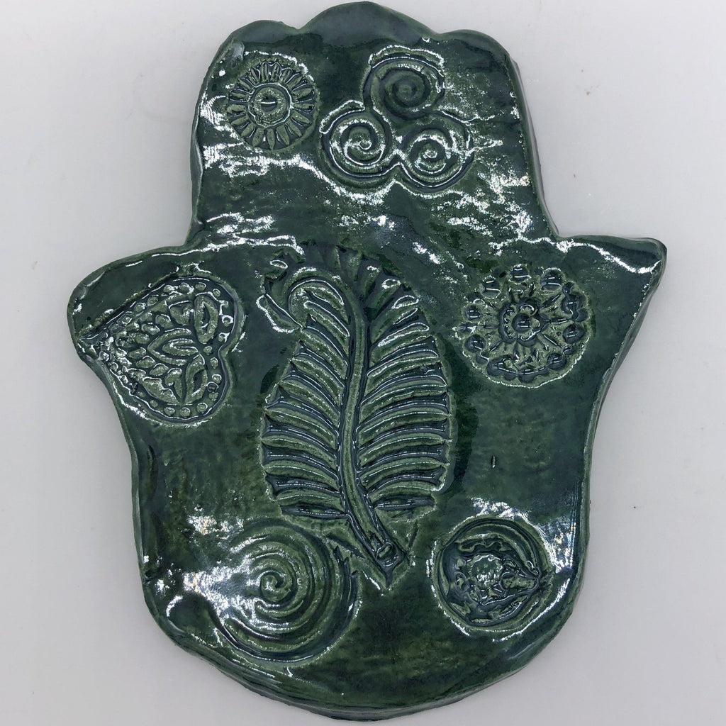 Shiny dark green clay hamsa with leaf, swirls and heart designs.
