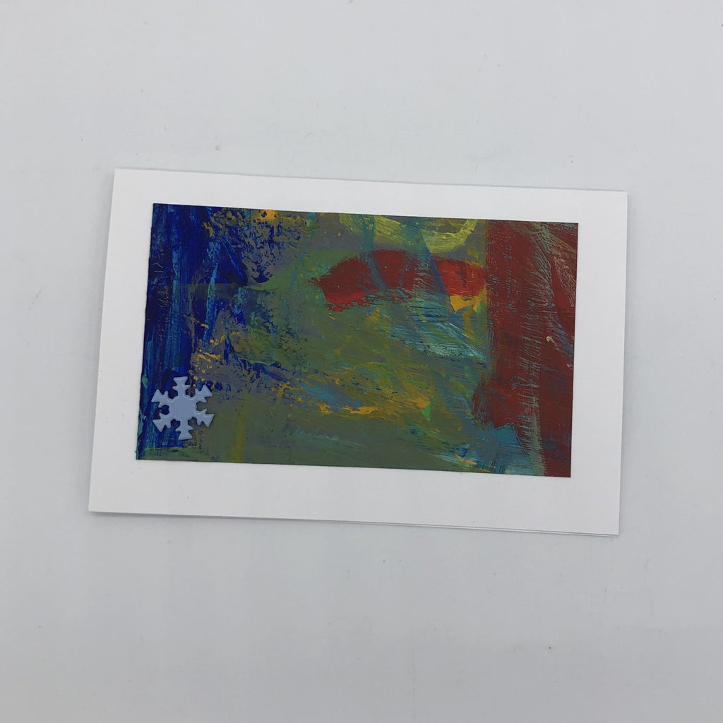 White greeting card with acrylic painting in blue and red with yellow mixed in.  Lower left hand corner has a light blue metal snowflake glued on.