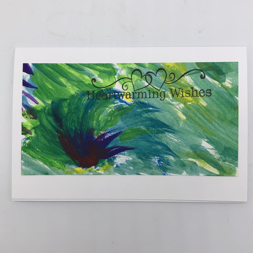 White greeting card with shade of blue and green painted on top is lines.  There is a dark blue cluster resembling a tuft of grass in the lower left hand corner.  On the top portion of the painting, flush to the right is the stamp in black that says Heartwarming Wishes and has two outlined hearts touching with flourishes to each side.