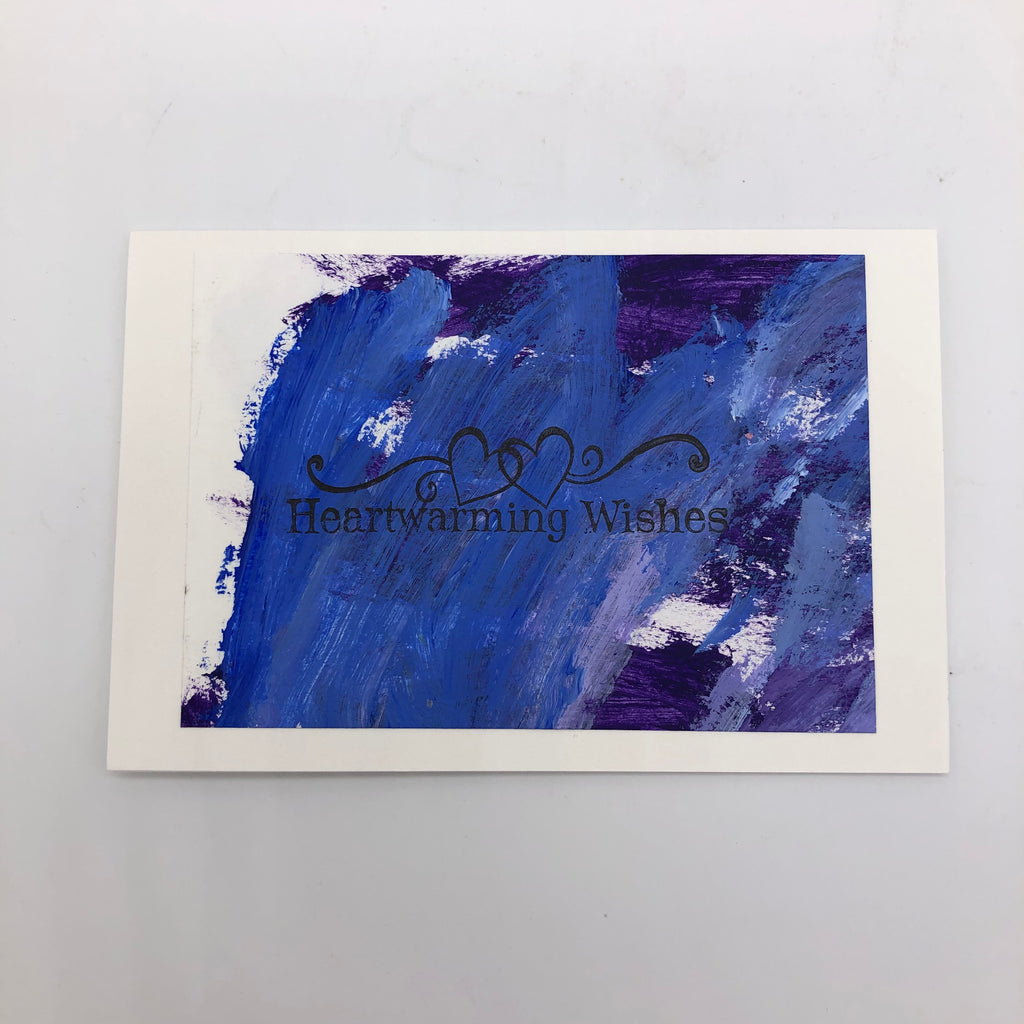 "White greeting card with purple acrylic painted on top.  THere is a stamp that says ""Heartwarming wishes in the middle and two outline hearts with flourishes to either side."