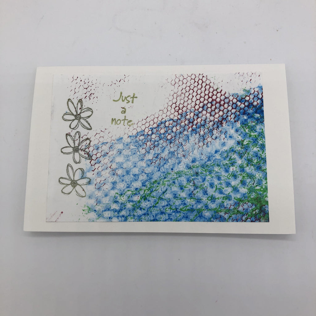 "White greeting card with rubbings of a textured net material in green and maroon.  There is also a large swatch of lined up circle texture in blue.  On top of the texture are three stamped outlined daisys in black and the words ""Just a note"" in green."