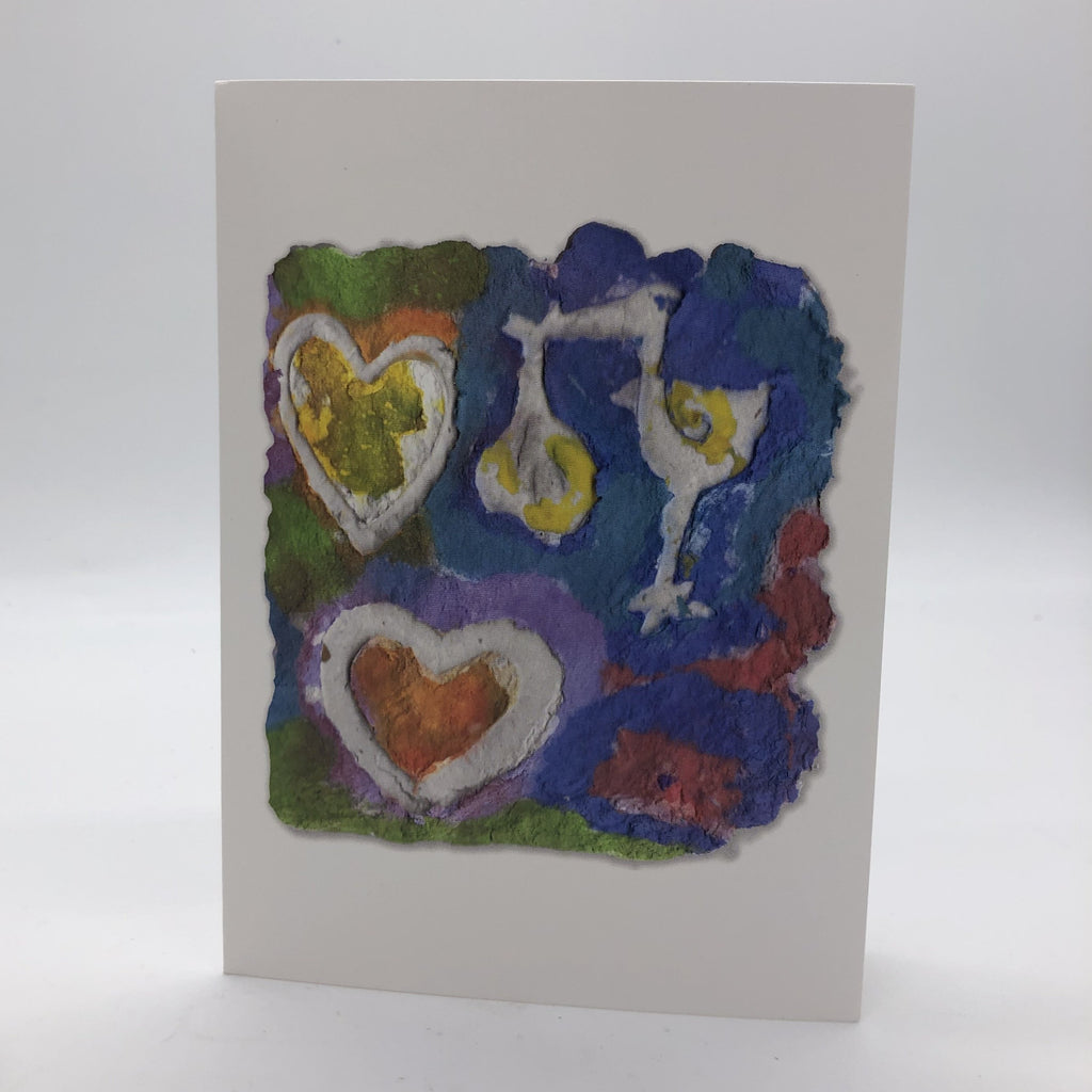 Printed card of photo of handmade paper in blues, greens and reds. On top of the design are two white hearts and a stork holding a wrapped baby by it's beak.