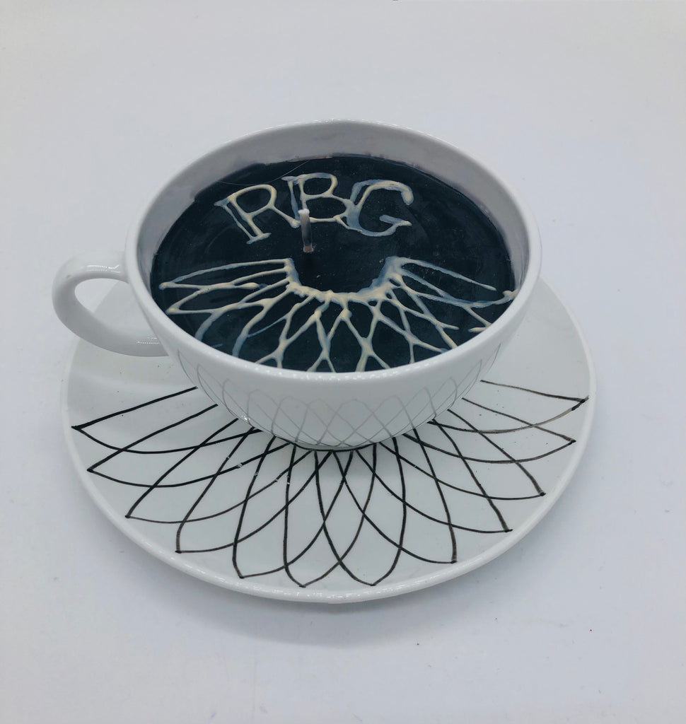 Solid white teacup and saucer with black candle inside.  On top of candle it says RBG and a lace collar.  The saucer has a drawn lace collar..