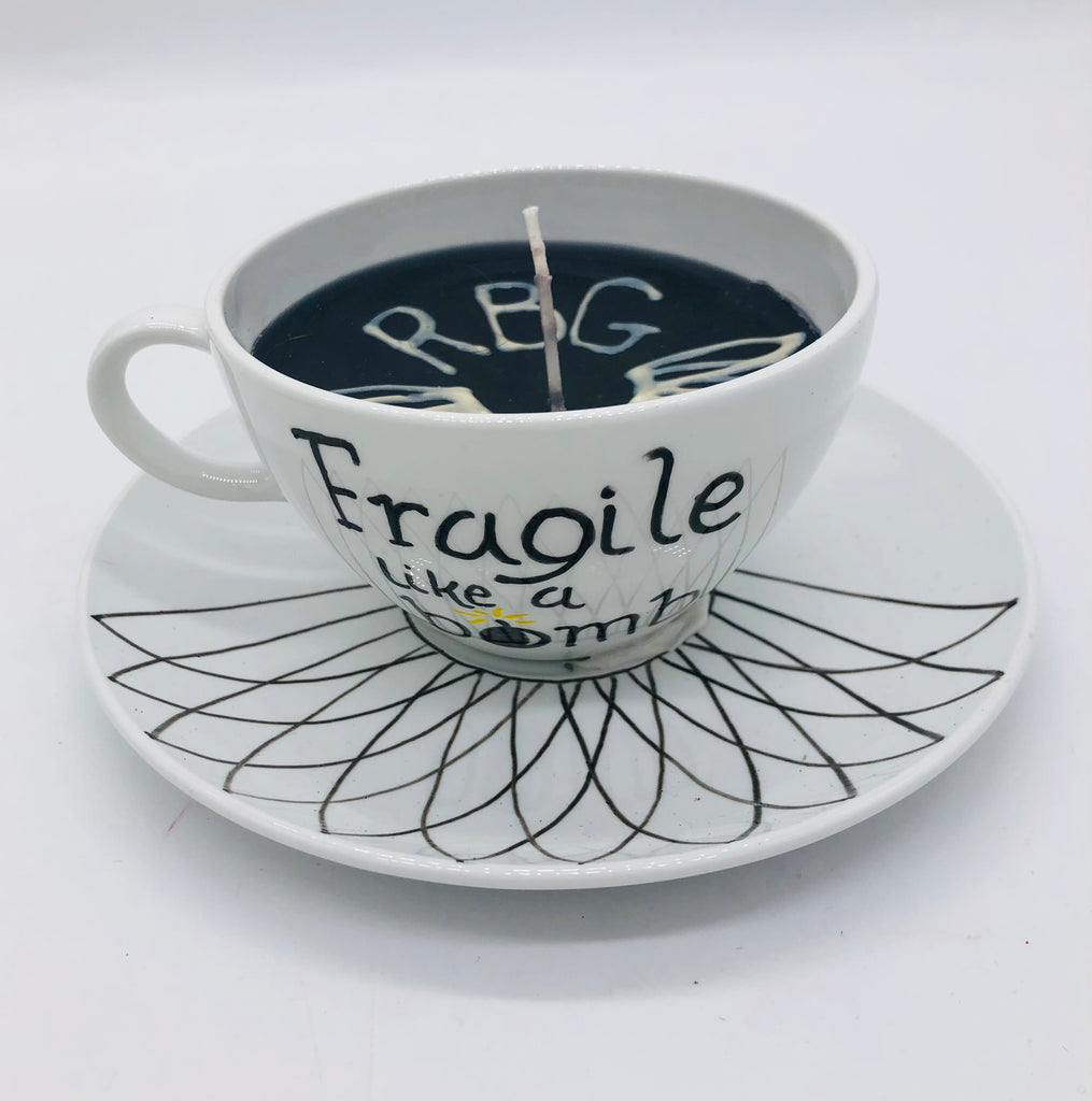 Solid white teacup and saucer with black candle inside.  On top of candle it has a lace collar and RBG.  The side of the cup says Fragile like a bomb..  The saucer says has a drawn lace collar.