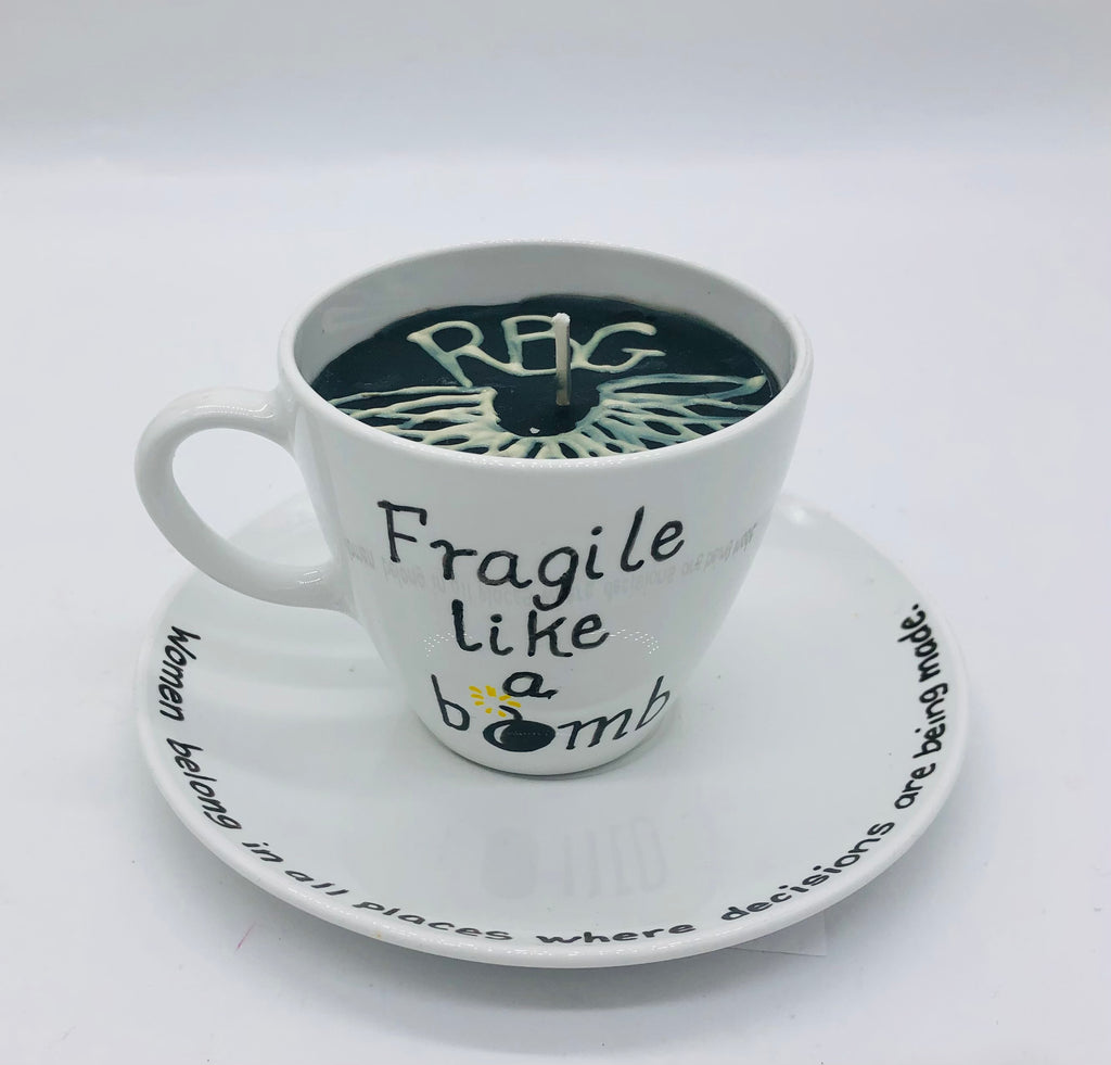 Solid white teacup and saucer with black candle inside.  On top of candle it says RBG and a lace collar.  On the side of the cup is says Fragile like a bomb and on the saucer is says Women belong in all places where decisions are being made.