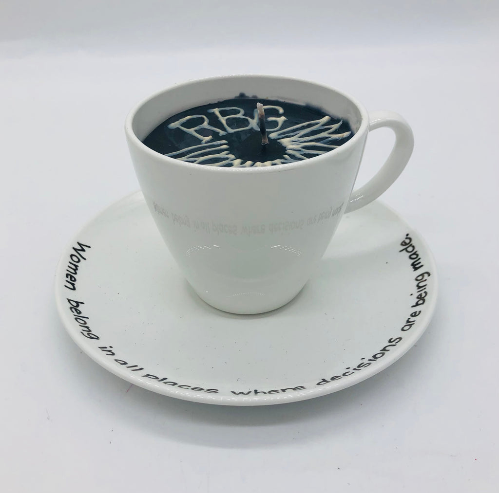 Solid white teacup and saucer with black candle inside.  On top of candle it has a lace collar and RBG.  The saucer says Women belong in all places where decisions are being made.
