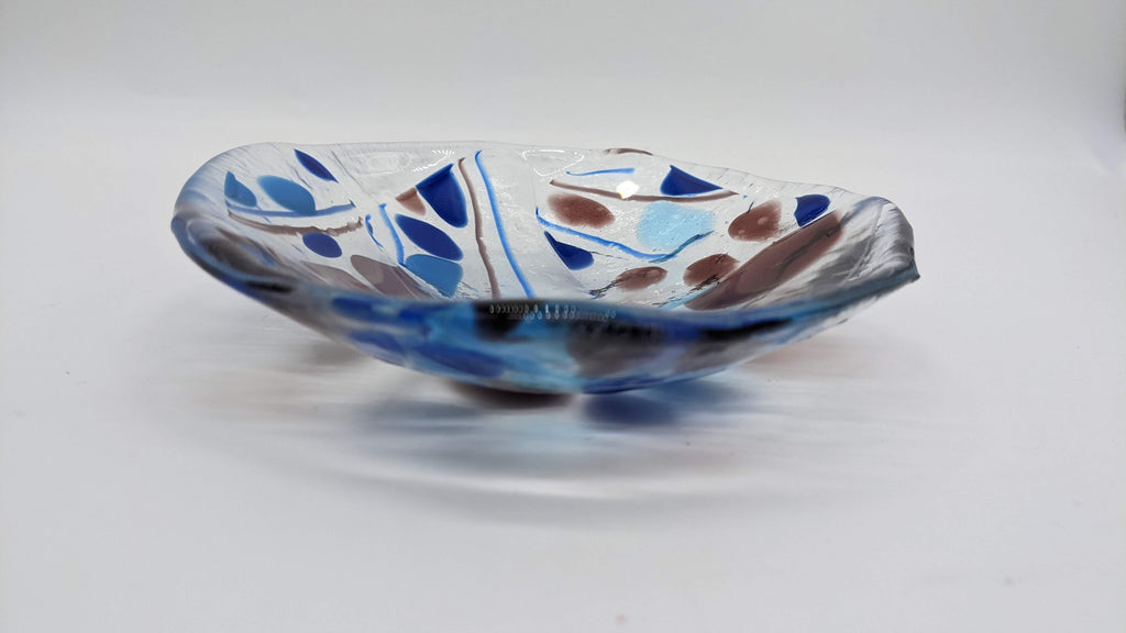 Clear glass bowl with specs of purple and blues through out