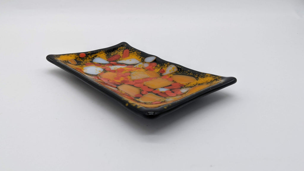Fused glass soap dish. Shades of orange against a black base