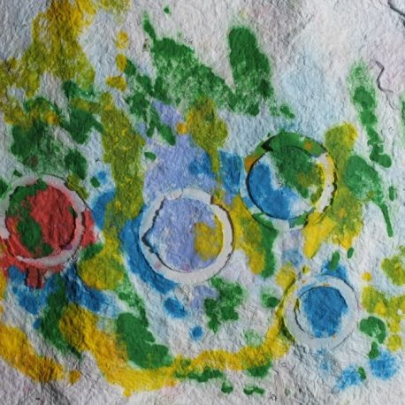 Pigment on recycled paper artwork with white circles against a mostly white background with small accents of yellow, green, red and blue
