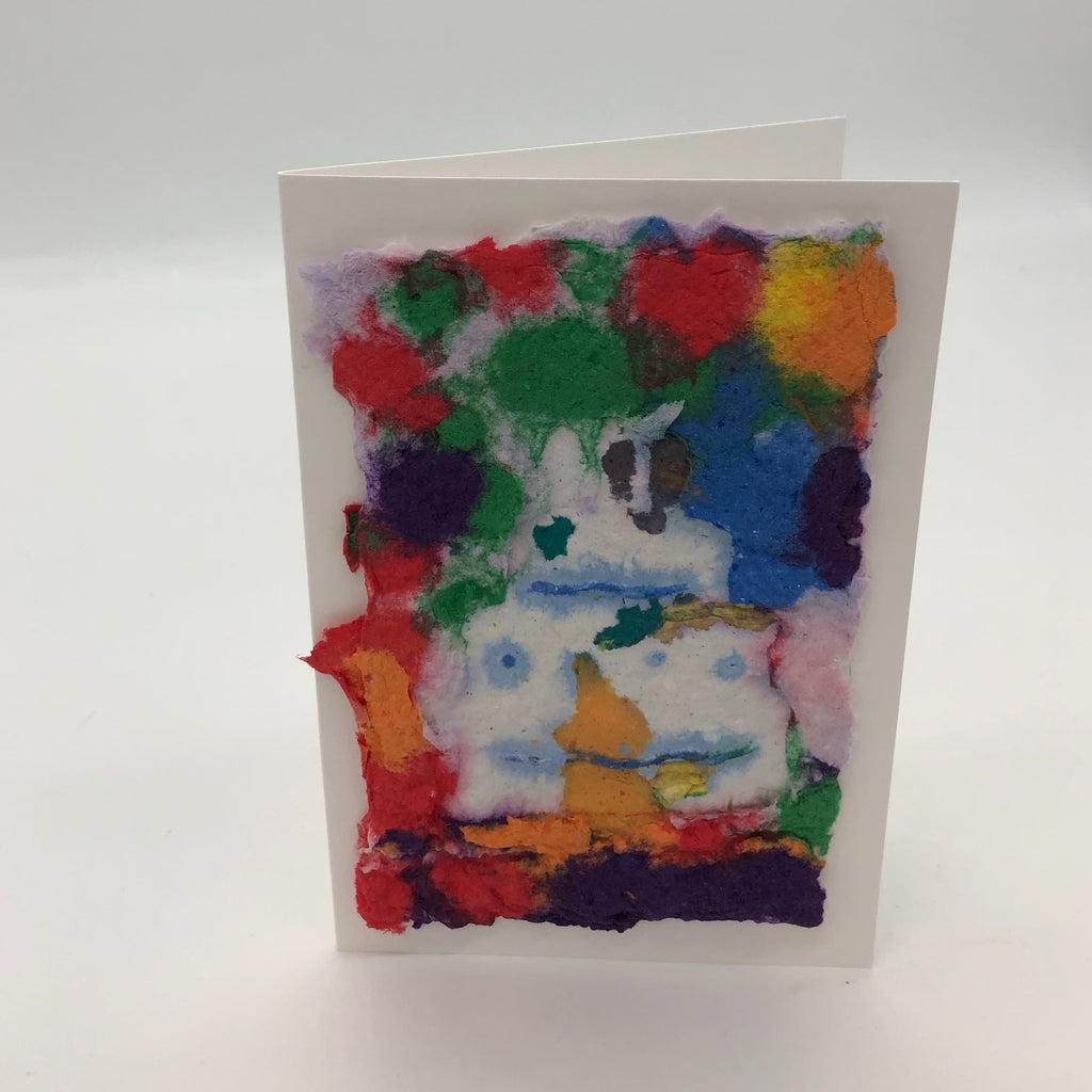 Handmade paper with white cakewith light blue details on top.  Background is blobs of several different colors including red, green, blue, purple, orange and yellow.