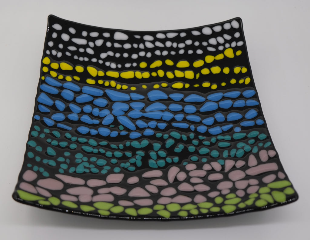 A black square glass curved plate that has small pebbles of colors. There are on average of three rows each color before transitioning to the next color. Colored pebbles are placed in the following order: white, yellow, blue, turquoise, light purple, and green.