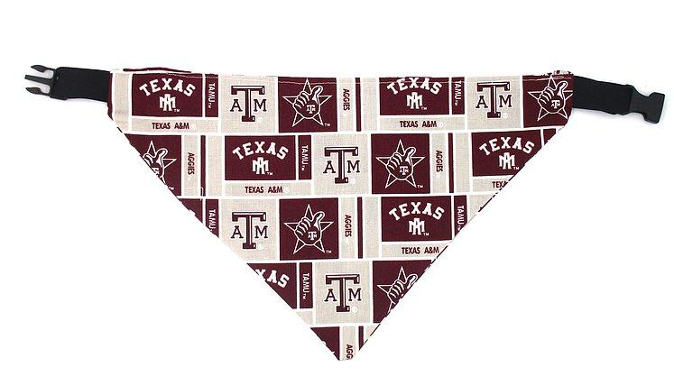 Photo of triangular dog bandana with black plastic closure.  Background of fabric is light gray with several maroon boxes with the A&M logo, the Gig Em graphic, Aggies and TEXAS in maroon.