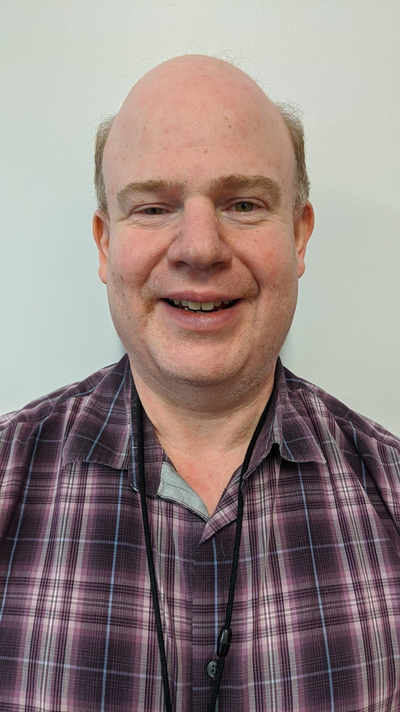 older man with receding hairline, smiling. Wearing a plaid colored shirt