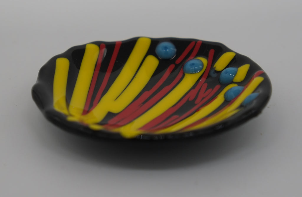 Small glass bowl for holing earrings. Lines of Yellow and Red radiating from corner with five blue dots on the opposite side