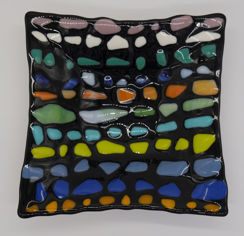 Black Glass square bowl with chunks of similar colors in rows. Starting at the top, light purple, white, teal, blue, orange, green, light blue, lime, blue, royal blue, and orange