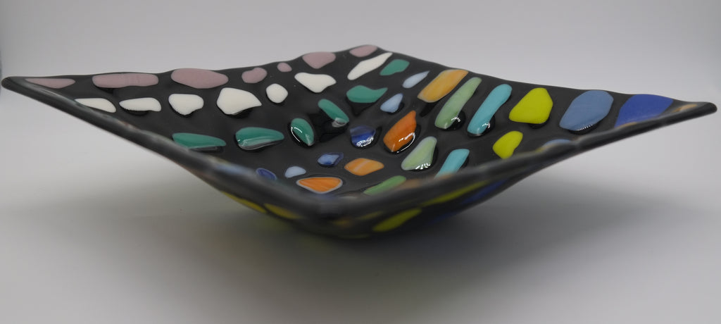 Side view of: Black Glass square bowl with chunks of similar colors in rows. Starting at the top, light purple, white, teal, blue, orange, green, light blue, lime, blue, royal blue, and orange