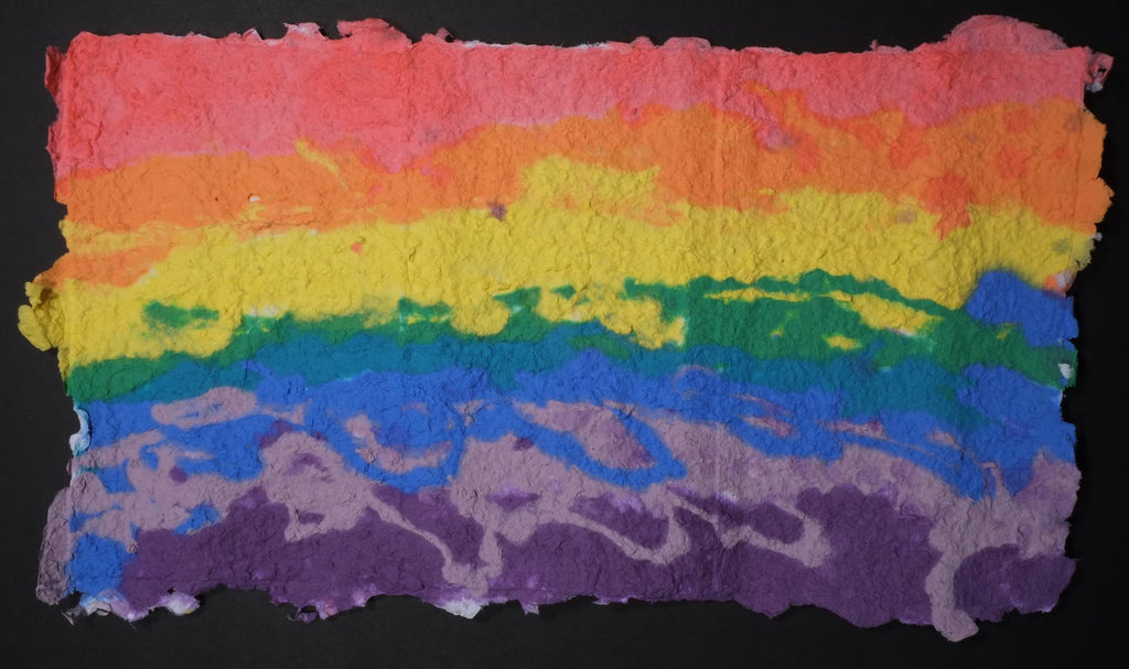 Highly textured handmade paper with horizontal lines of color (starting at the top) red, orange, yellow, green, blue, light purple, and dark purple.
