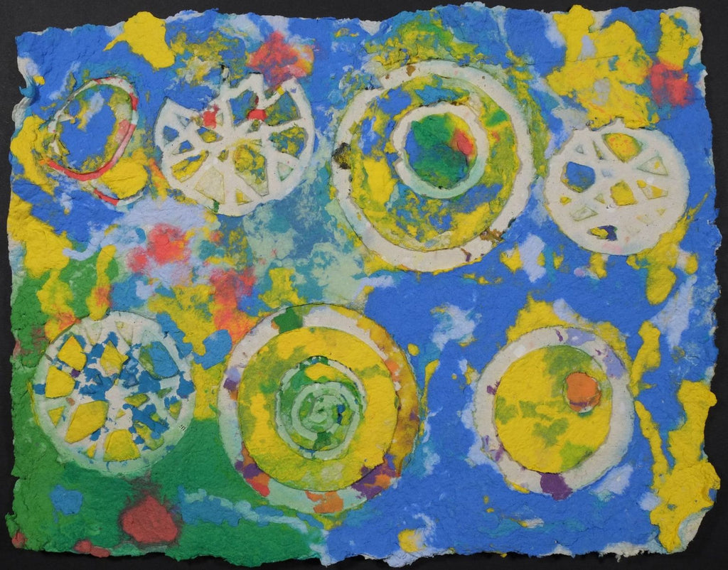 Pigment on recycled paper artwork with white circles, swirls and wagon wheels against a background of blue, yellow, green and red
