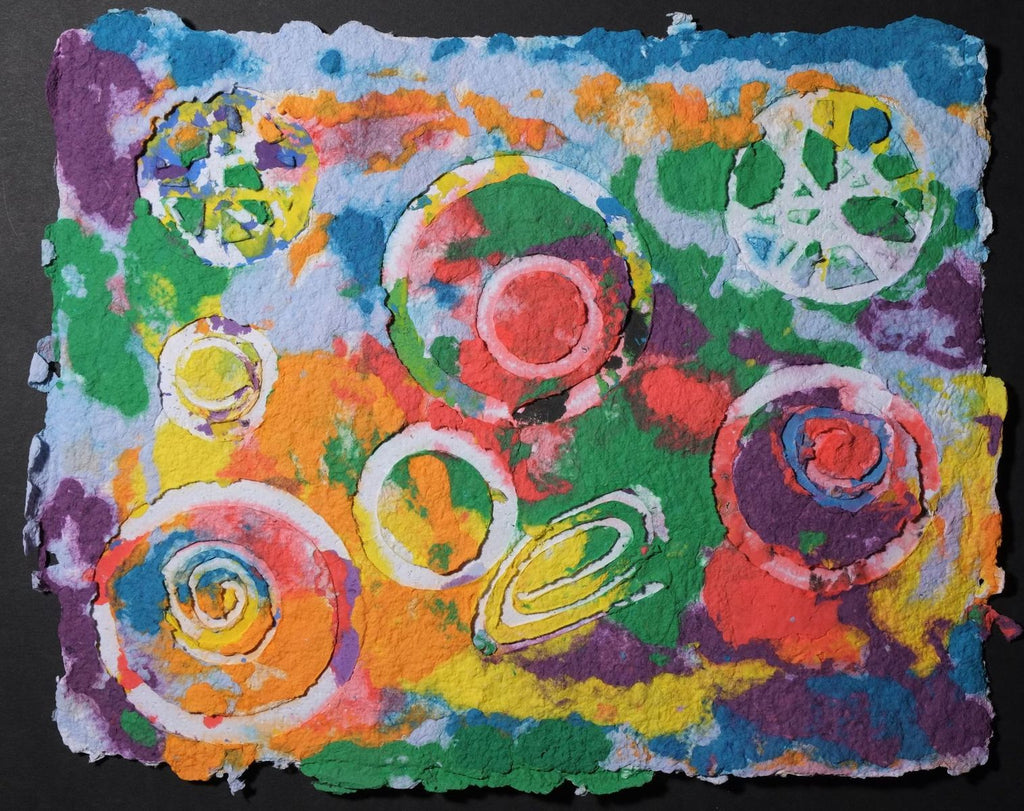Pigment on recycled paper artwork with white circles, swirls and wagon wheels against a background of melted colors of blue, purple, green, red, orange and yellow