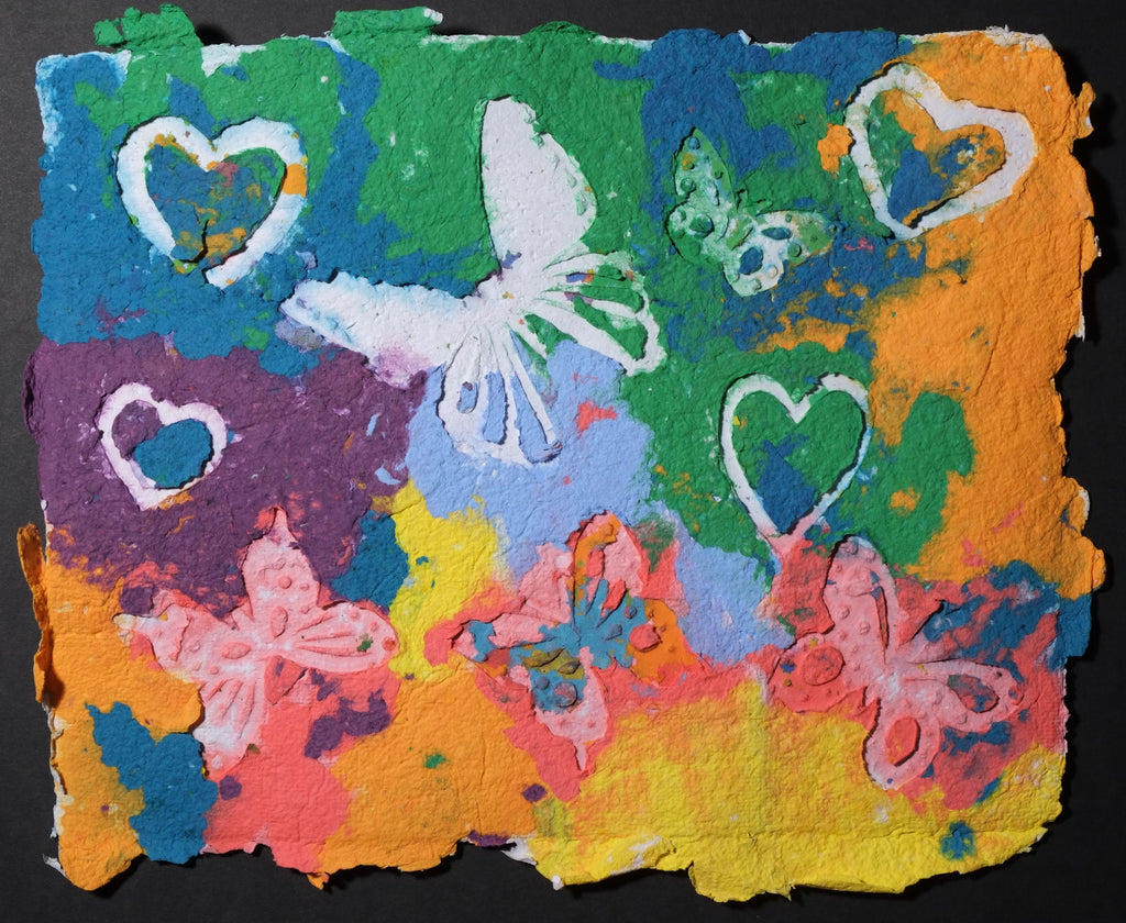 Highly textured handmade paper with white embossed butterflies and hearts against brightly colored oranges, greens, reds, and purple.