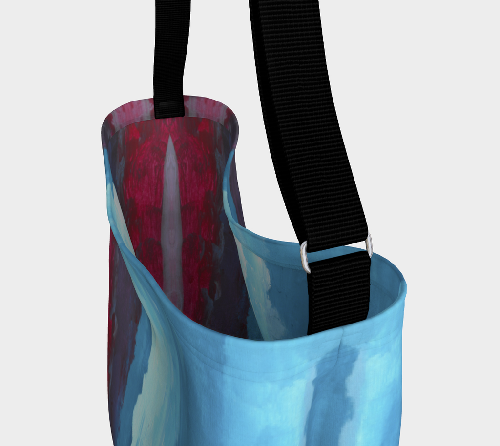 Close up photo of Crossbody bag showing black strap with red, light blue and dark blue gradient design
