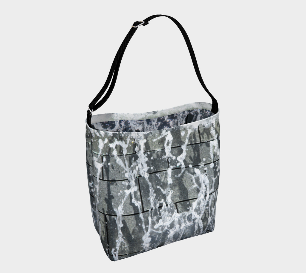 Crossbody tote with black strap with gray, white and black design depicting running water